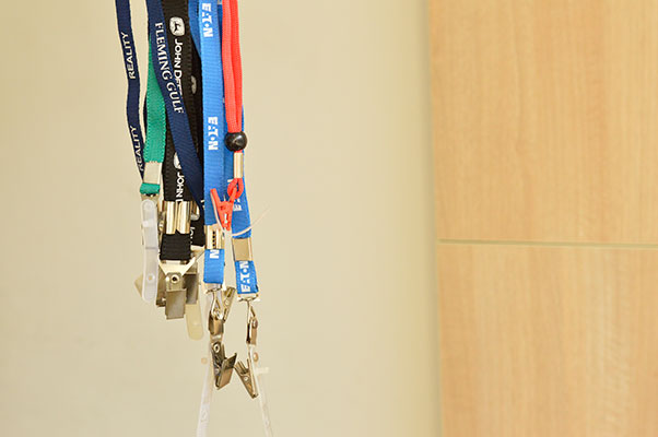 collection of lanyards with company logos printed on them